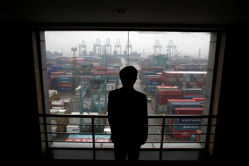 An employee views the Port of Shanghai from an office window.