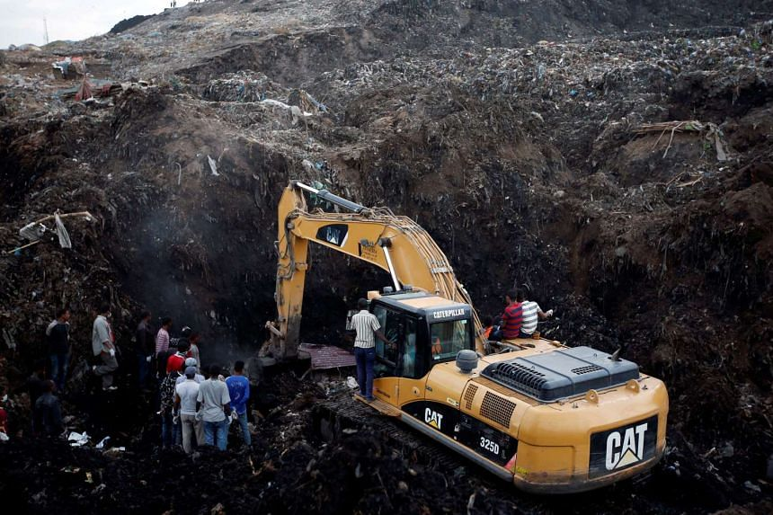 Rescue workers watch as excavators dig into a pile of garbage in search of missing people at the landslide.