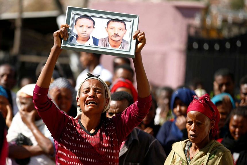 Civilians react as they watch the search for missing people following the landslide at the Koshe garbage dump in Ethiopia's capital Addis Ababa