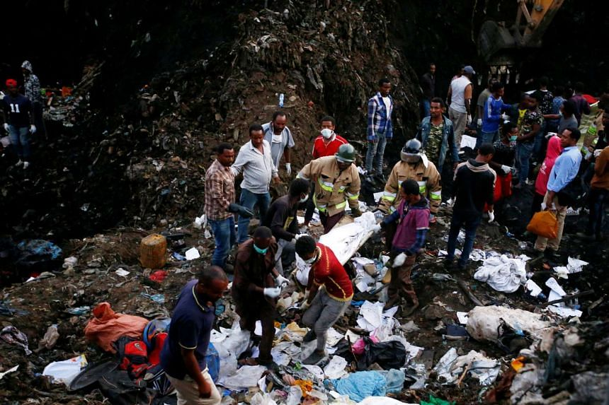 Rescue workers carry the body of a victim from the landslide at the garbage dump.