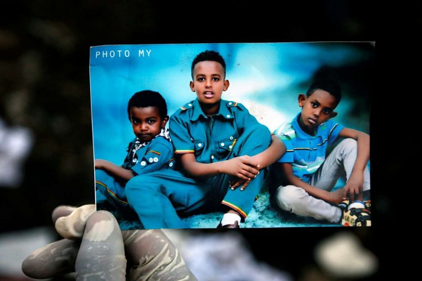 A rescue worker holds a photograph of children suspected to be missing at the garbage dump landslide.