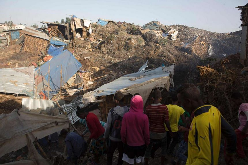 People look at the damage done to dwellings built near the main landfill of Addis Ababa on March 12, 2017, after the deadly landslide.