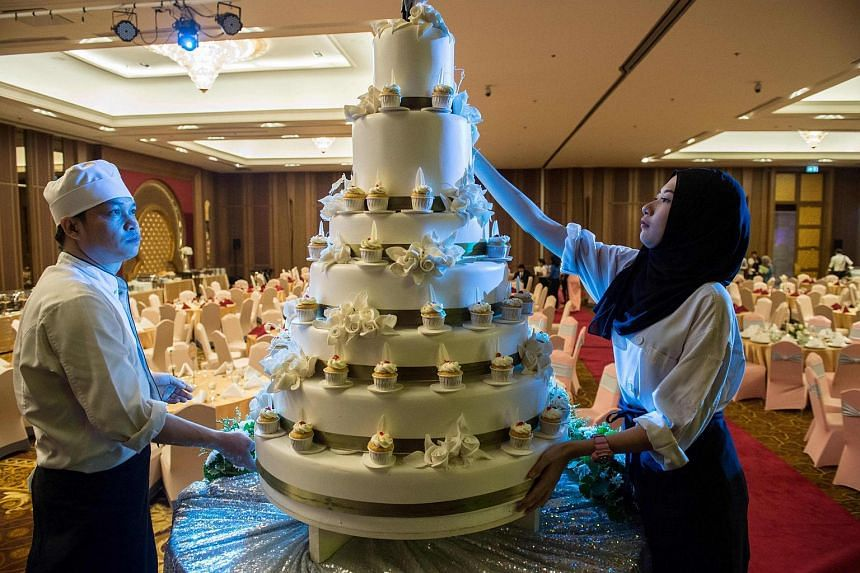 Pastry chefs adorn a wedding cake before a wedding reception at the Al Meroz hotel in Bangkok.