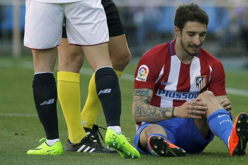 Atletico de Madrid's Croatian defender Sime Vrsaljko (R) is injured in the first minute of the play against Sevilla during their Spanish Primera Division soccer game at Vicente Calderon stadium, in Madrid, Spain on March 19, 2017.