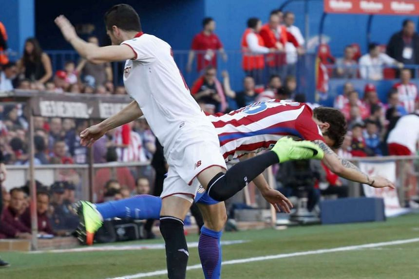 Atletico de Madrid's Croatian defender Sime Vrsaljko (right) vies for the ball with Sevilla's defender Sergio Escudero during their Spanish Primera Division soccer game at Vicente Calderon stadium, in Madrid, Spain, on March 19, 2017.