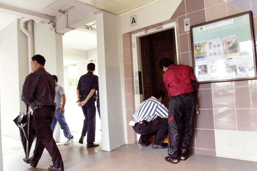 Policemen inspecting the lift where the body of Ms Soh San was found.