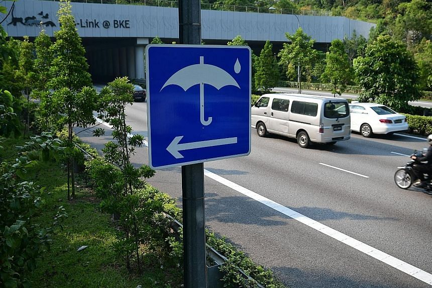 A rain shelter sign along the Bukit Timah Expressway (BKE). A rain shelter for motorcyclists on the BKE, one of 80 at the 10 expressways here. Such shelters are marked by umbrella signs and demarcated by vehicle impact guard rails or spring-loaded po