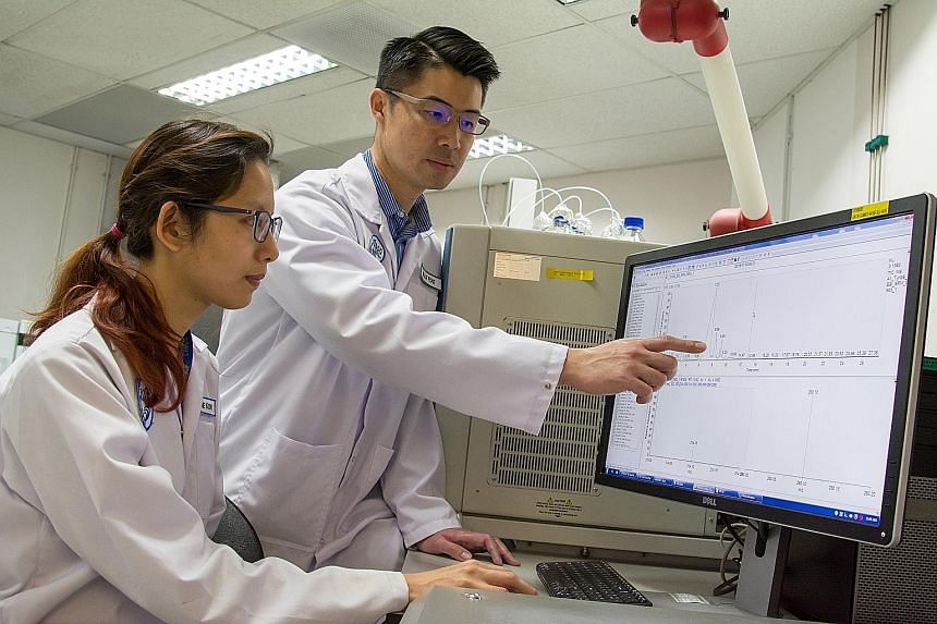 Mr Willy Foo, a senior member of DSO's technical staff, and Ms Serene Koh, a defence scientist, looking at the molecular signatures of a chemical being analysed.