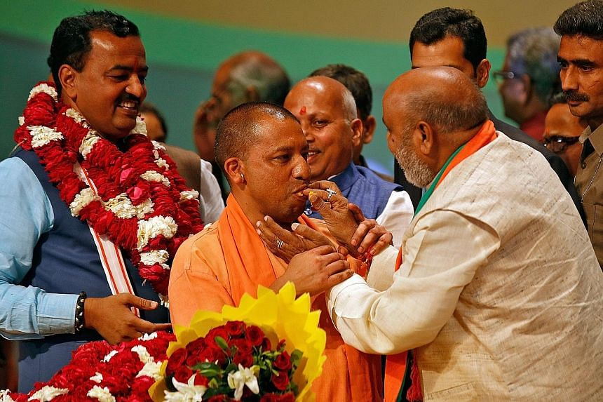 Mr Yogi Adityanath being offered sweets at a BJP legislative party meeting at the Uttar Pradesh capital of Lucknow last Saturday, after he was elected chief minister of the state. Analysts expect his appointment to test the strength of the party's co