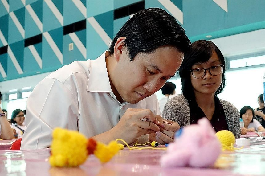 Marsiling-Yew Tee GRC MP Alex Yam putting the final touches to a crochet doll yesterday as part of a project that aims to raise awareness of children with cancer. He is accompanied by Ms Chong Hui Min, 17, a cancer survivor. About 150 cancer survivor
