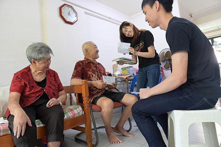 NUS students Joel Chan, 25, and Tan She Hui, 24, with Telok Blangah residents Goh Chek Eng, 74, and his wife, Madam Chia Cho Kheow, 72. The students helped to check the couple's medical appointment letters.