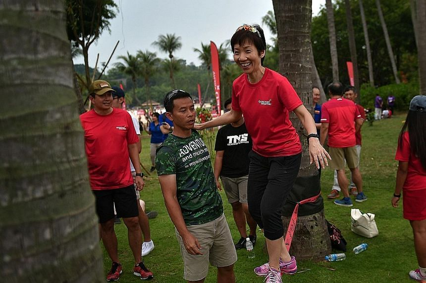 Above: Minister Fu slacklining at Sentosa. Like tightrope walking, slacklining involves balancing and walking on a line anchored on both sides above ground level. Left: National ultimate frisbee player Janssen Tan (in red) and former national player