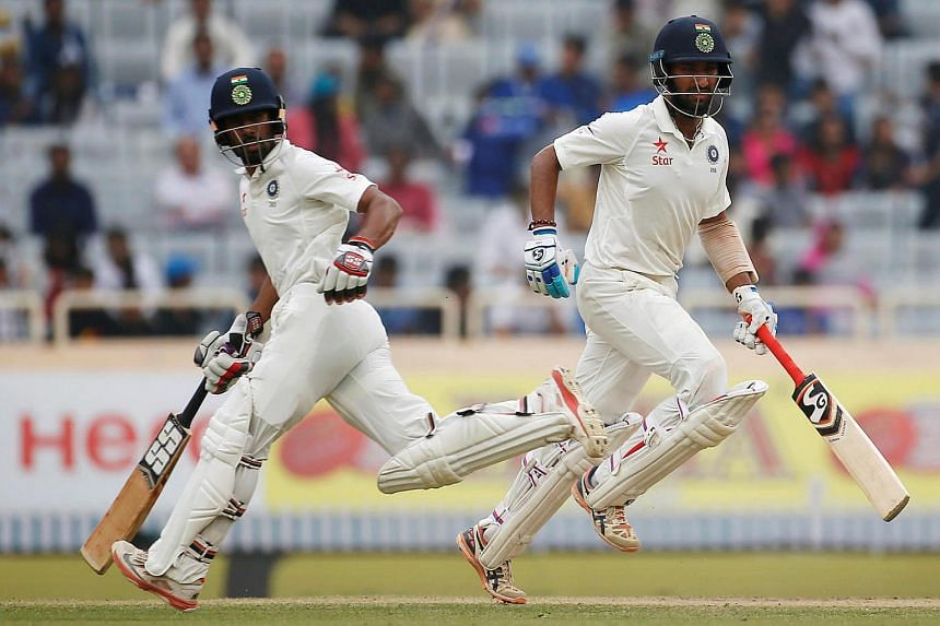 India's Cheteshwar Pujara (right) and Wriddhiman Saha run between the wickets during their cricket match between India and Australia, on March 19, 2017.