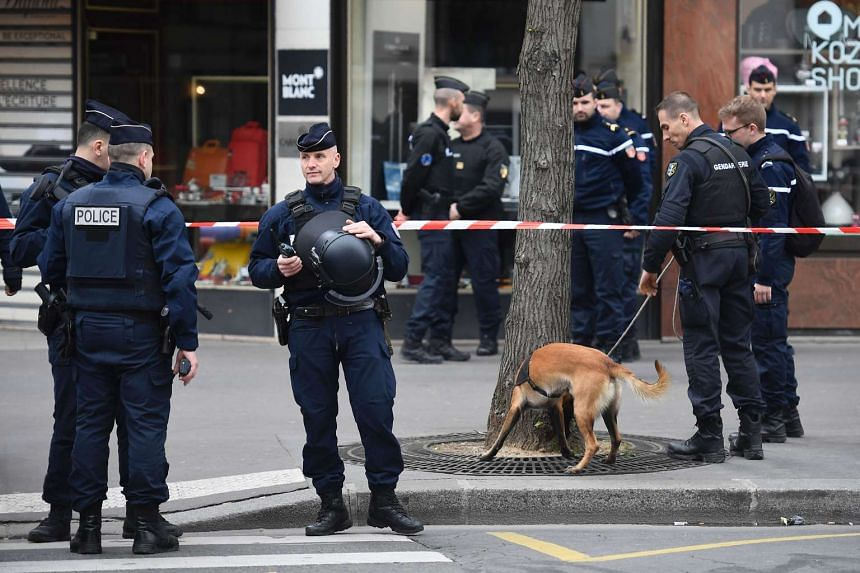 French police officers standing guard at a cordoned off area in front of the financial crimes court building in Paris on March 20, 2017.