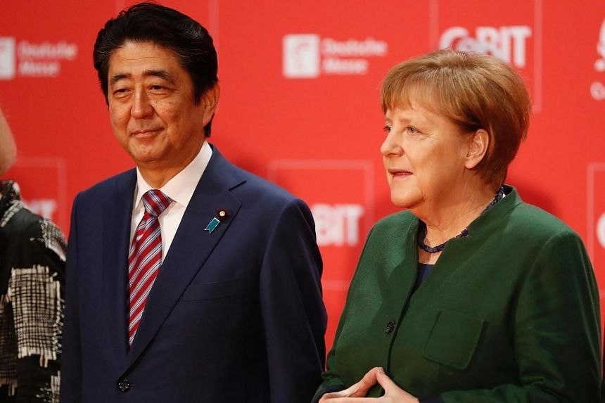 German Chancellor Angela Merkel (right) arrives with Japanese Prime Minister Shinzo Abe at the official opening of the CeBIT technology fair in Hanover.