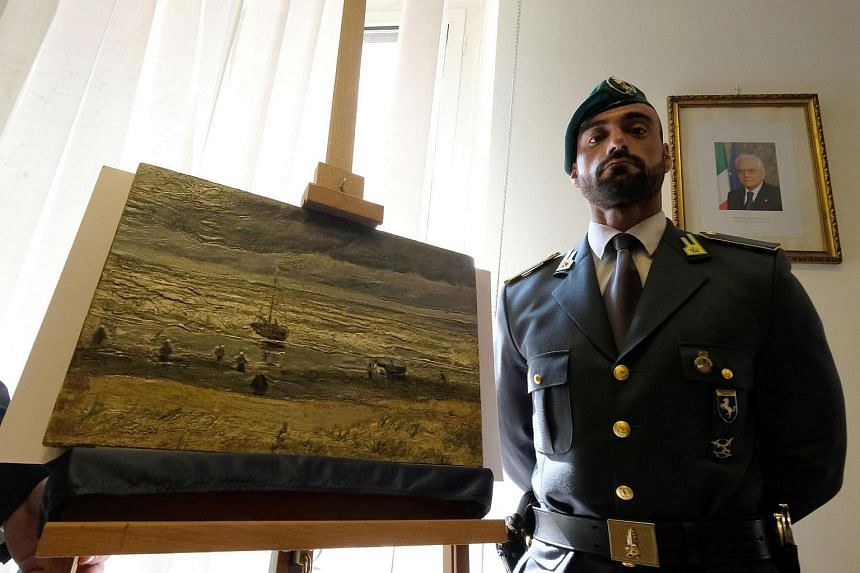 File photo taken on Sept 30, 2016, shows an Italian policeman standing next to next to one of two recovered stolen paintings by late Dutch artist Vincent Van Gogh entitled The Beach At Scheveningen During A Storm in Naples.