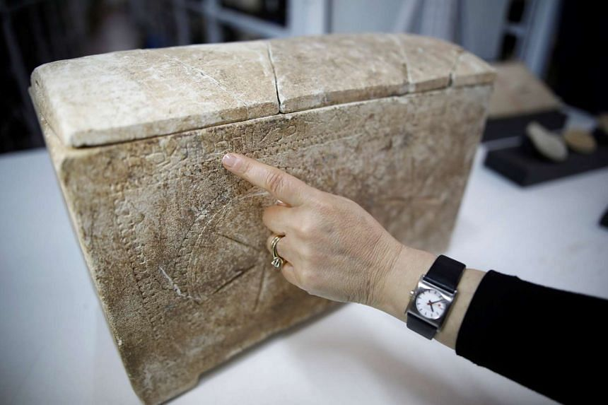 """An archaeologist points to an ossuary with the inscription in Hebrew that says: """"Miriam daughter of Yeshua Son of Caiaphas, Priests [of] Ma'aziah from Beth-Imri""""."""