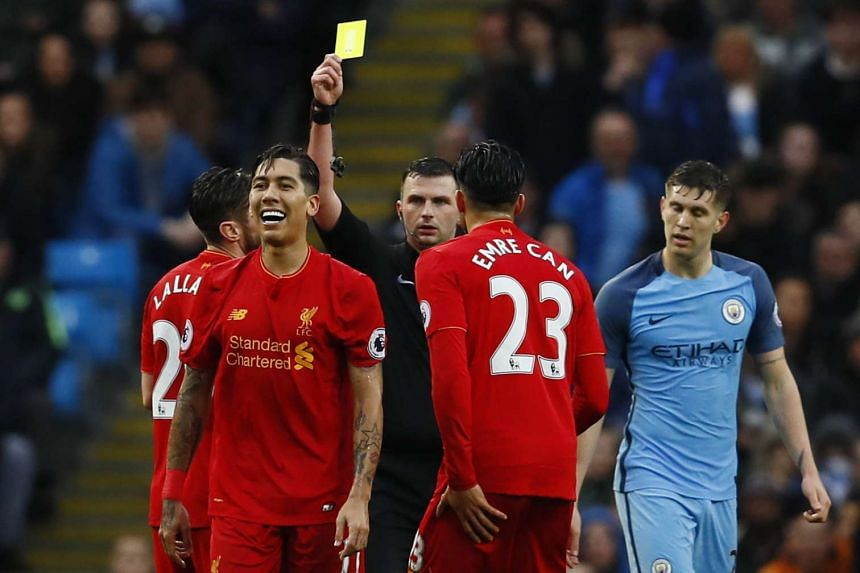 Referee Michael Oliver was surrounded by City players after he awarded Liverpool a spot kick following a Gael Clichy foul on Roberto Firmino.