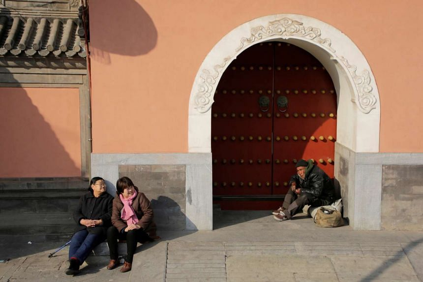 A homeless man sitting at an entrance of a temple next to residents in central Beijing.