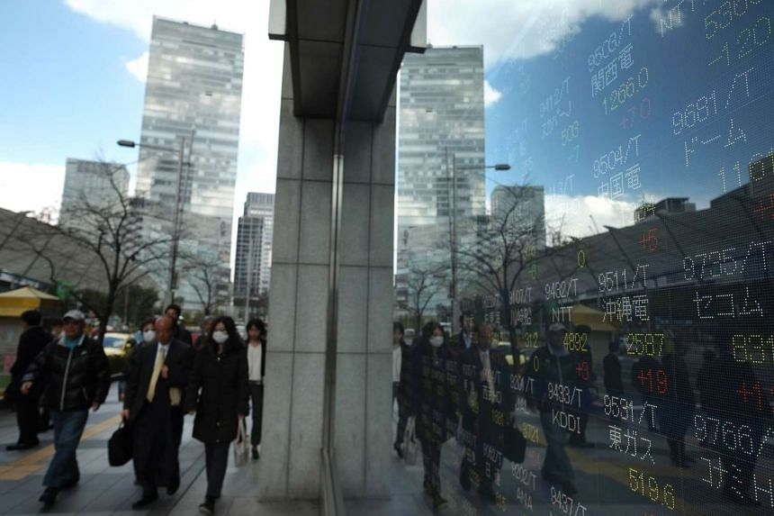 Pedestrians walk next to an electric quotation board flashing the Nikkei key index of the Tokyo Stock Exchange (TSE) in front of a securities company in Tokyo.