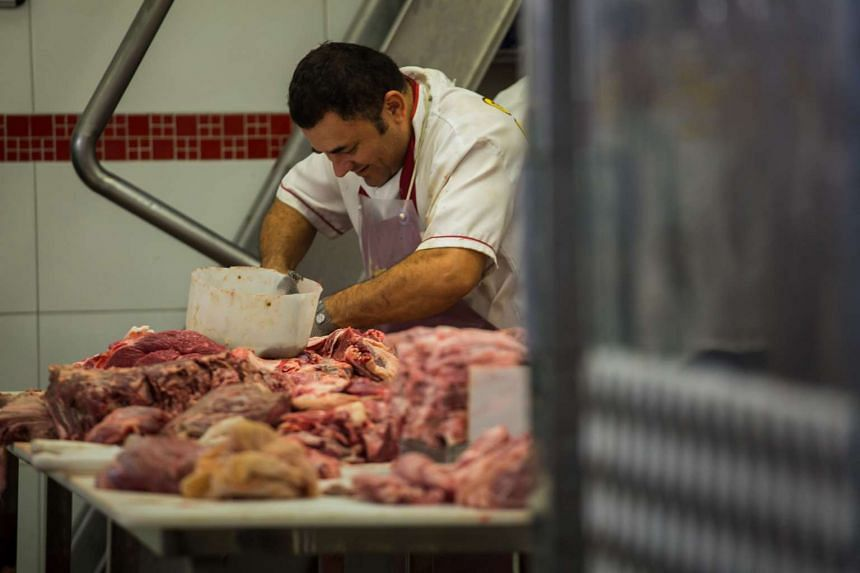 A butcher cuts meat at a butchery stall inside a market in Sao Paulo, Brazil, on March 18, 2017.