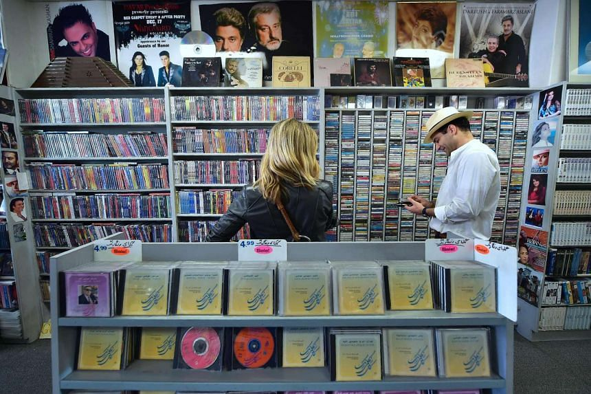 Iranian-American Arash Saedinia (right), an English literature professor and writer at UCLA, browses for music at the Music Box along Westwood Boulevard.