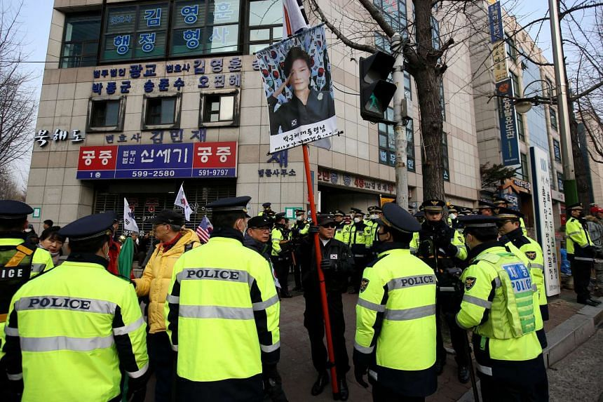 A supporter of former South Korean President Park Geun Hye holds a banner featuring an image of Park during a protest outside the prosecutors office in Seoul, South Korea, on Tuesday, on March 21, 2017.