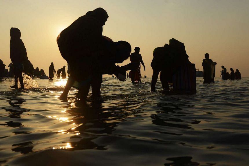 Hindu devotees performing rituals at Gangasagar Island, at the confluence of the River Ganges and the Bay of Bengal, on Jan 15, 2017.