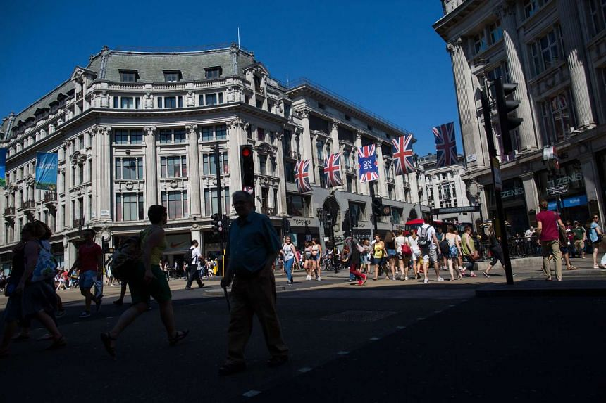 Pedestrians cross the road at Oxford Circus and underneath British union flags in London. Consumer prices in Britain rose by a stronger-than-expected 2.3 per cent in annual terms, the largest increase in over three years.