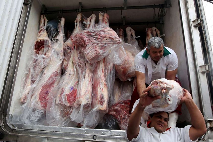 Workers unload packed meat from a truck in Sao Paulo, June 3, 2015.