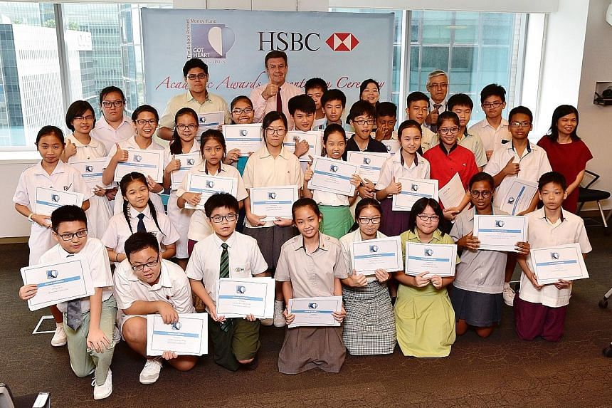 Among the Straits Times School Pocket Money Fund beneficiaries who received cash awards for doing well in the PSLE are Chong How (front row, left) and Dhaniyah Qasimah Zamri Abdullah (front row, second from right). In the back row are HSBC chief exec