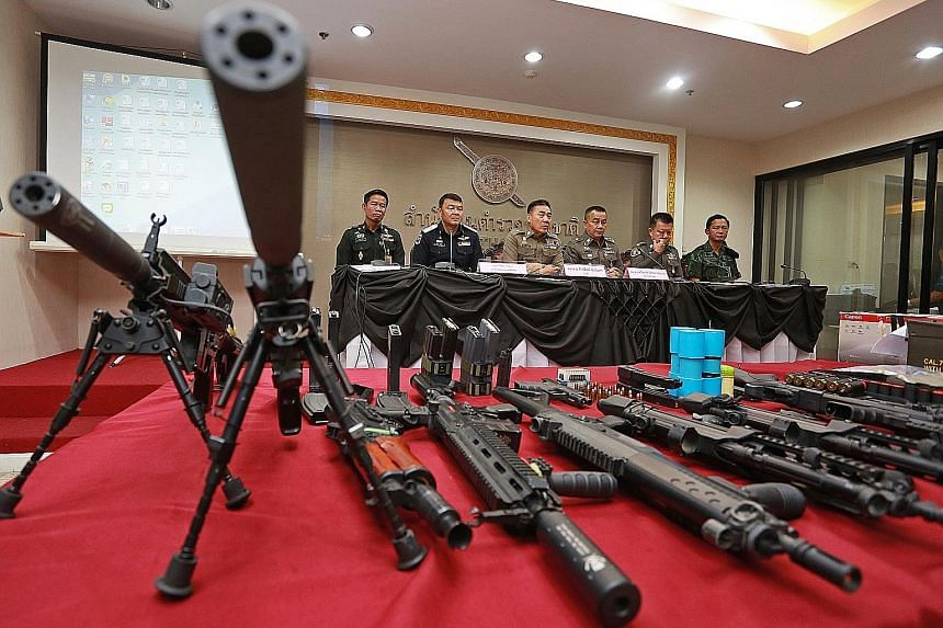 """Police chief Chakthip Chaijinda (third from left) speaking to the media on Sunday. In the foreground are weapons seized from a house which police say used to be occupied by fugitive """"red shirt"""" activist Ko Tee."""