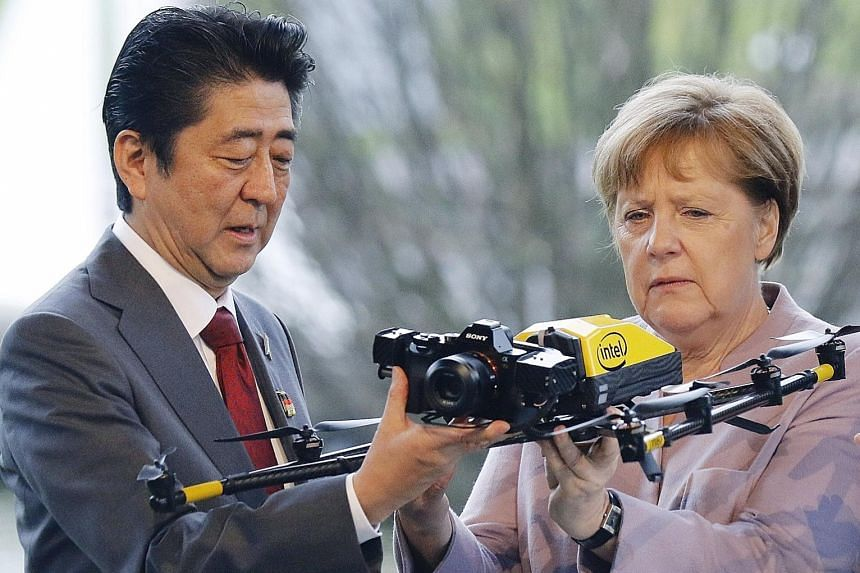 Japanese Prime Minister Shinzo Abe and German Chancellor Angela Merkel examining a drone at the Intel booth yesterday at the opening of the CeBIT computing trade fair in the German city of Hanover. More than 3,000 exhibitors from 70 countries are dis