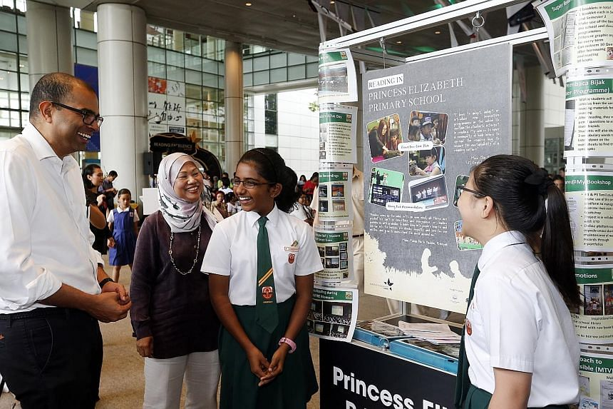 Dr Puthucheary and Madam Moliah with Princess Elizabeth Primary School pupils Deekshanya Kugesh and Bevery Chong Jia En, both 12, at the school's booth during the Reading Excellence Awards ceremony yesterday. The school's reading programme won it the
