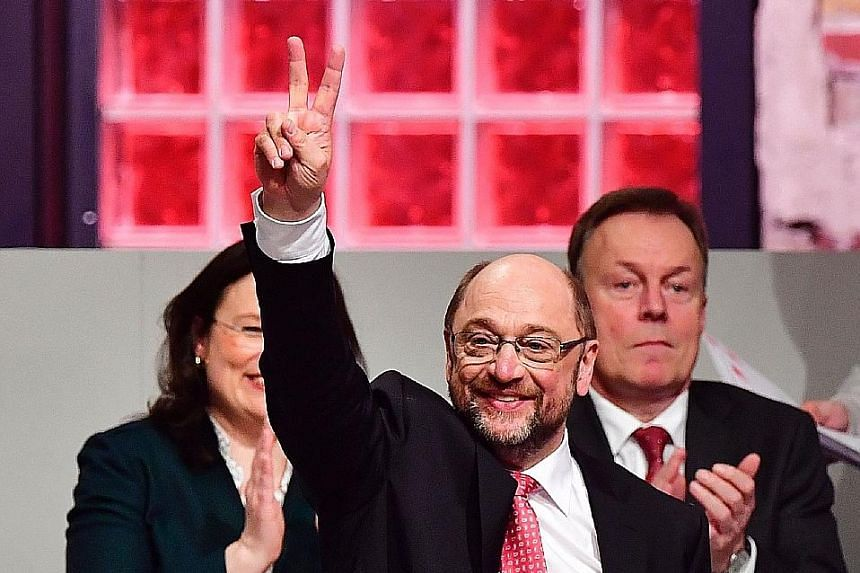 Mr Schulz acknowledging his victory after becoming the SPD leader on Sunday. He supports free education, more investment in nursing care and schools, and qualification programmes for the unemployed.