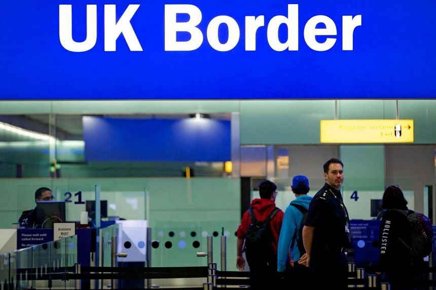 A border patrol officer stands at the British Border crossing in the Terminal 2 at Heathrow Airport in London.