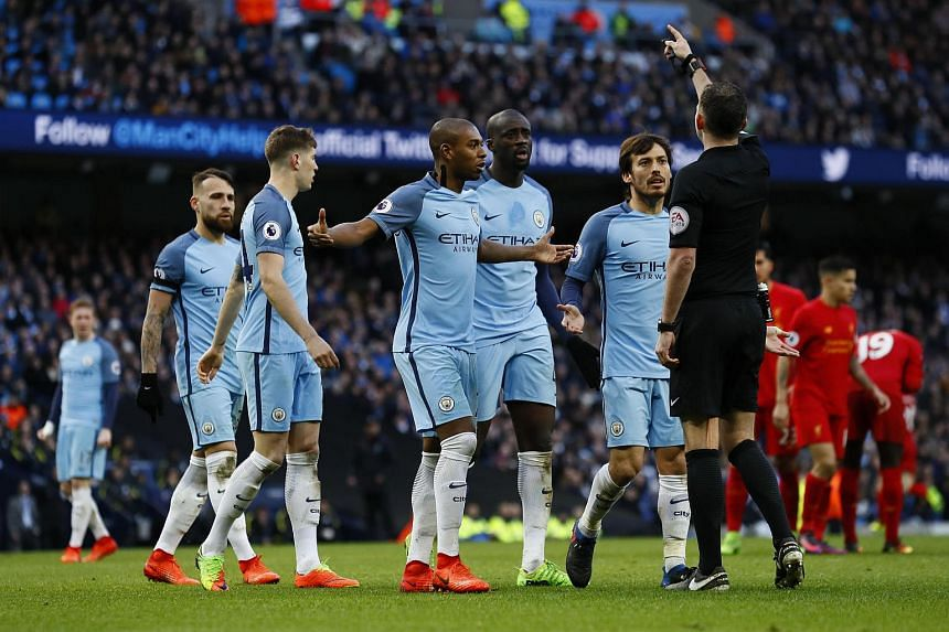 Referee Michael Oliver speaks to Manchester City's David Silva (right) and team mates after awarding Liverpool a penalty.