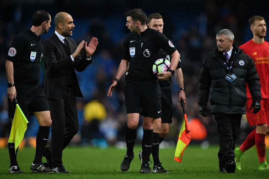 Manchester City manager Pep Guardiola (second from left) speaks with referee Michael Oliver after the match on Sunday (March 19).