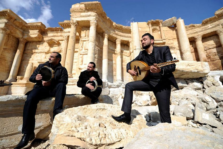 Syrian musicians play while resting on damage in the amphitheatre of Palmyra on March 4.