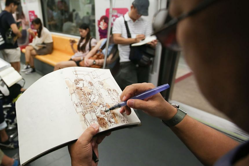 Mr Tan sketching on the train, while Mr Theo (above)  fills in his drawings with colour.