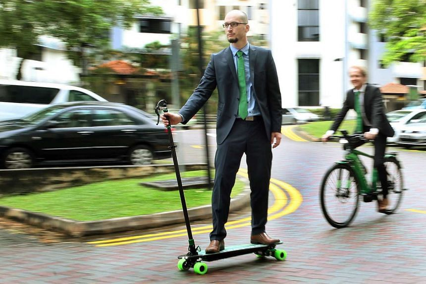 Dr Mayer taking a joyride on the Schaeffler e-board, an electric skateboard that can be steered, accelerated and braked using only one hand. Meanwhile, Mr Andreas Schick, CEO Asia-Pacific, Schaeffler, demonstrates an electric bicycle with a built-in autom