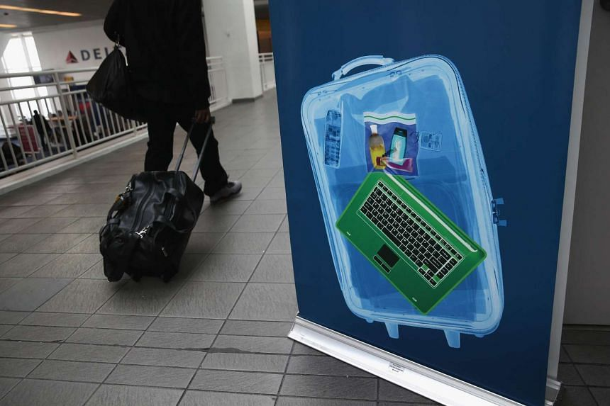 A traveller walking past a newly-opened TSA Pre-check application centre at LaGuardia Airport. The US is banning all electronic devices larger than an average-sized mobile phone.
