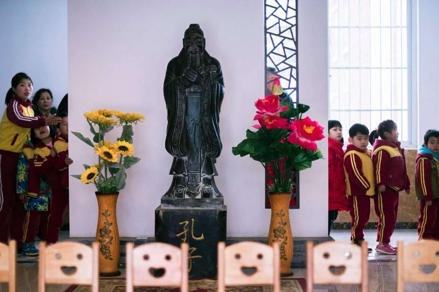 Children lining up behind a statue of Confucius after a class at a Confucius kindergarten in Wuhan, China.