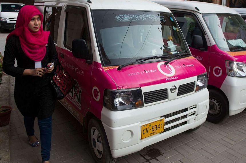 A driver with the women-only Paxi Pakistan taxi company walking past a Pink Taxi during a launching ceremony in Karachi on March 8, 2017.