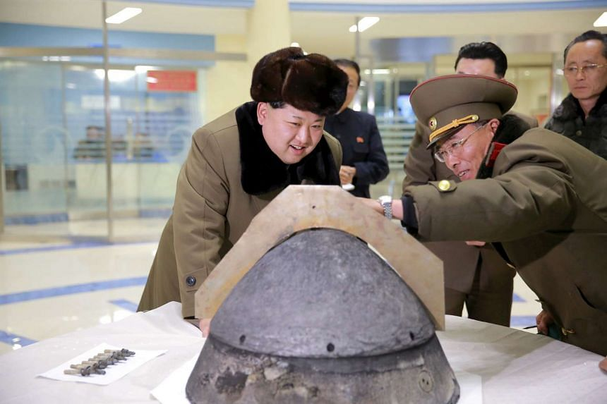 An undated photo released by North Korea's Korean Central News Agency of North Korean leader Kim Jong Un (left) looking at a rocket warhead tip.