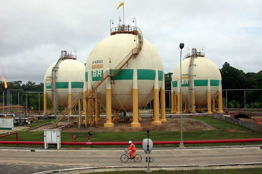 A Petroleo Brasileiro SA (Petrobras) worker cycling past natural gas storage tanks at the Araras production facility in the Urucu oil field.