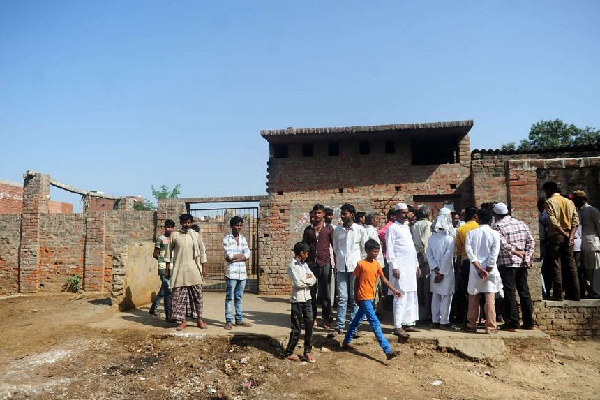 Indian Muslim butchers and traders with family members gather outside a closed illegal slaughter house at Naini in Allahabad.
