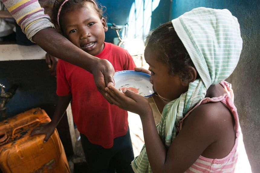 A young girl drinks water from a bowl at a public fountain during a period when public water supply has been cut off in the Isotry district of Antananarivo, Madagascar.