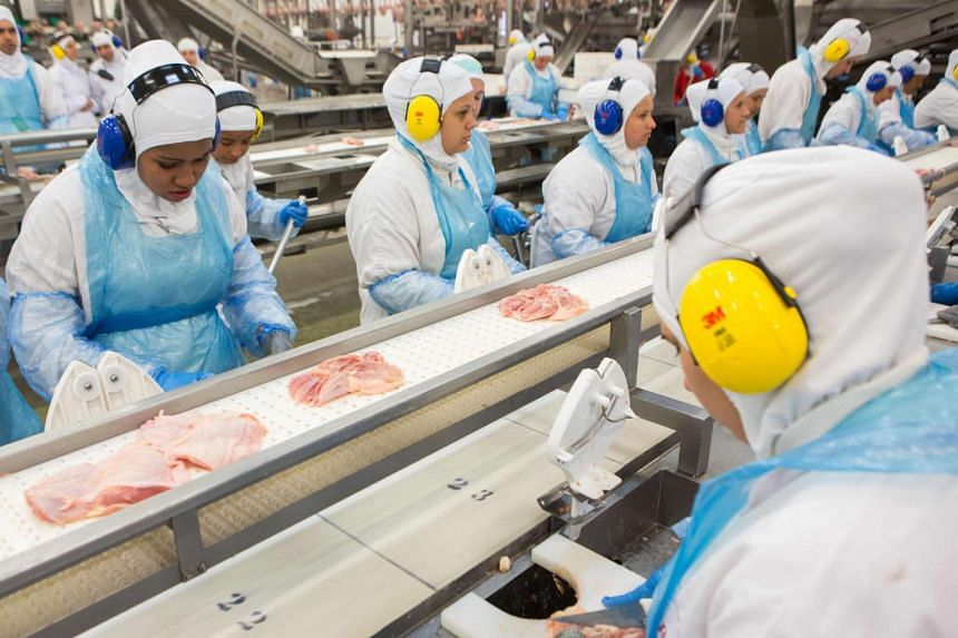Employees work on a production line at the JBS-Friboi chicken processing plant in Lapa, Parana State, Brazil.
