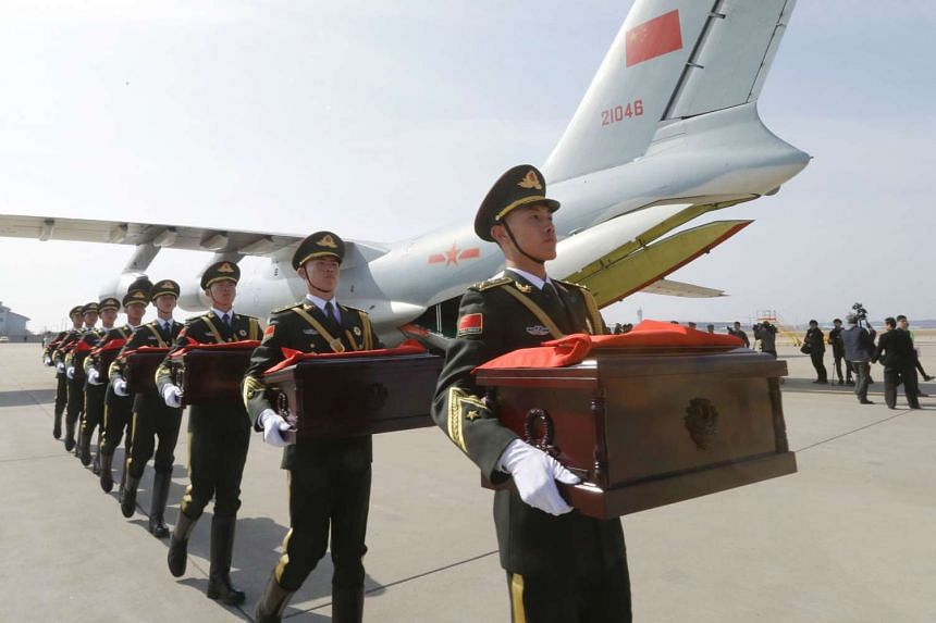 Chinese honor guards with caskets containing the remains of Chinese soldiers move into a cargo airplane during the handing over ceremony at the Incheon International Airport.